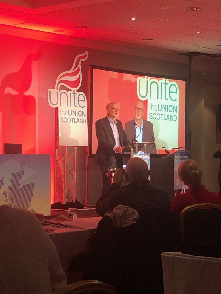 Jeremy Corbyn stood in front of a Unite the Union sign, at the podium of the Scottish Policy Conference